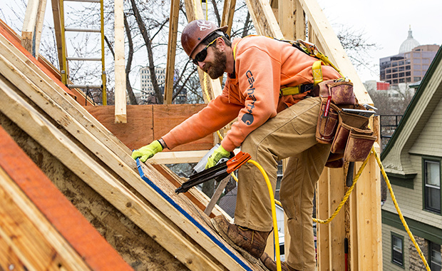 Chris Tatge working in safety gear on roof trusses at a jobsite